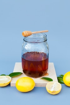Front view jar with honey surrounded by lemon