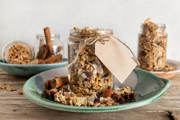 Vista frontale di barattoli sulla piastra con cereali per la colazione e tag