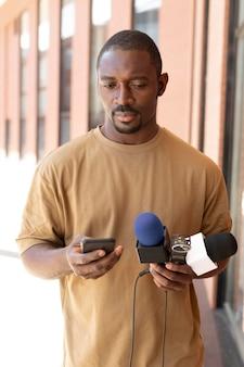 マイクを持っている正面のジャーナリスト