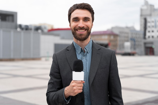 Журналист, вид спереди, держит микрофон