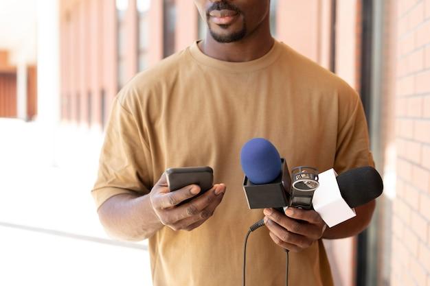 Giornalista di vista frontale che tiene un microfono