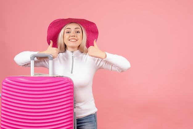 親指をあきらめるピンクのスーツケースと正面図うれしそうなブロンドの女性