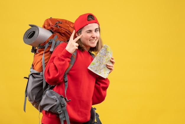 勝利のサインを作る旅行マップを保持している正面図うれしそうな女性のバックパッカー