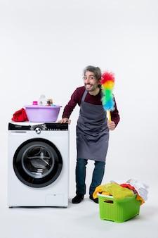 Vista frontale gioiosa governante che tiene in mano uno spolverino in piedi vicino al cesto della biancheria della lavatrice su sfondo bianco