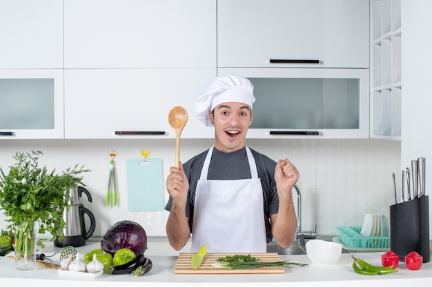 Front view joyful male chef in uniform holding wooden spoon behind kitchen table