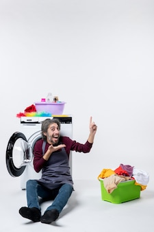Vista frontale gioiosa governante maschio seduta davanti al cesto della biancheria della lavatrice su sfondo bianco