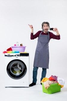 Vista frontale uomo gioioso che tiene la carta in piedi vicino alla lavatrice su sfondo bianco