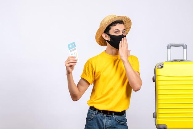 旅行チケットを保持している黄色のスーツケースの近くに立っている黄色のtシャツで楽しい観光客の正面図