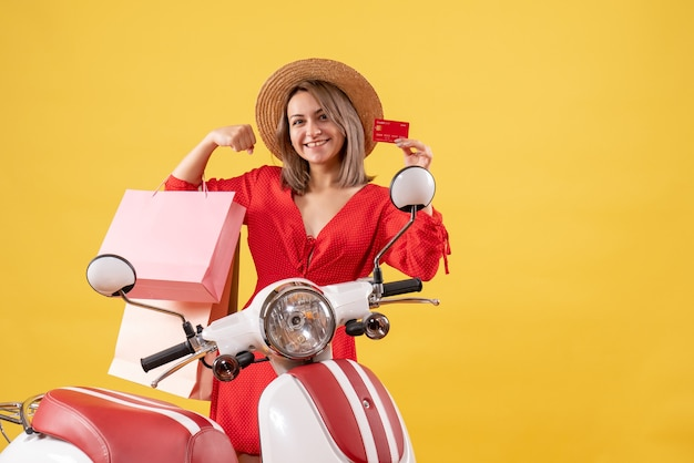 Front view of joyful woman in red dress on moped holding shopping bags and card