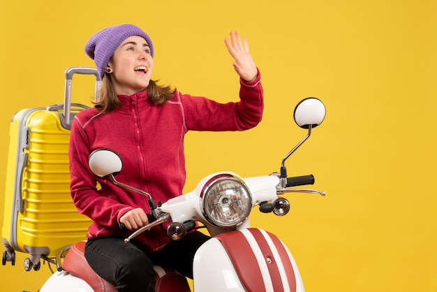 Front view joyful young girl on moped waving hand