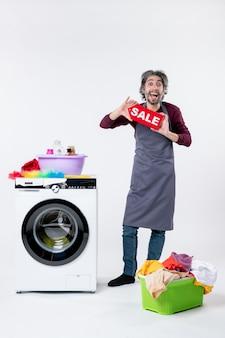 앞치마를 입은 즐거운 젊은 남자가 흰색 배경에 있는 세탁기 세탁 바구니 근처에 서 있는 판매 표지판을 들고 있습니다.