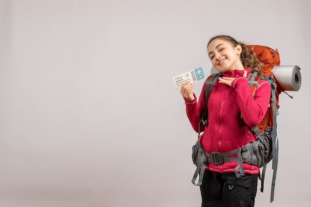Front view of joyful young traveller with big backpack holding up travel ticket on grey wall