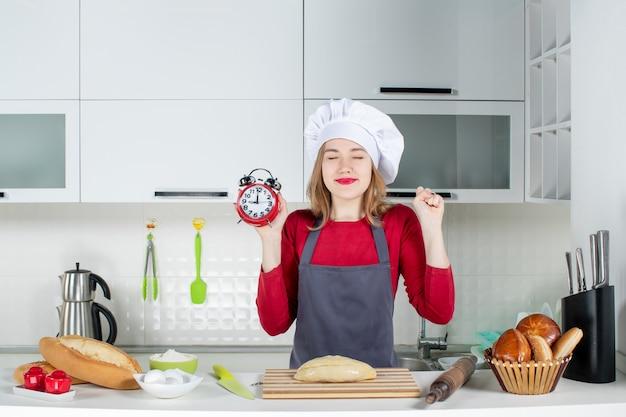 キッチンで赤い目覚まし時計を保持しているクック帽子とエプロンの正面図うれしそうな若い女性