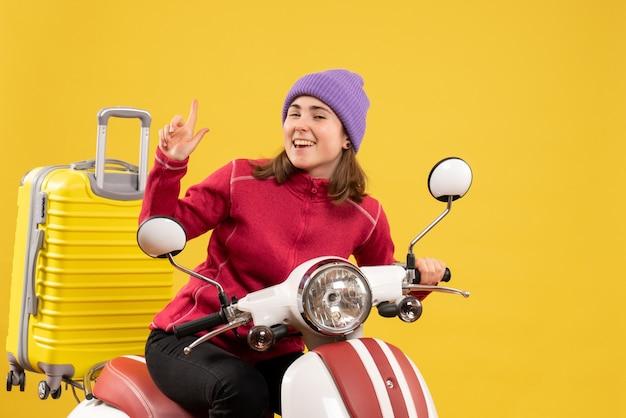 Vista frontale gioiosa giovane donna sul ciclomotore che punta il dito verso l'alto
