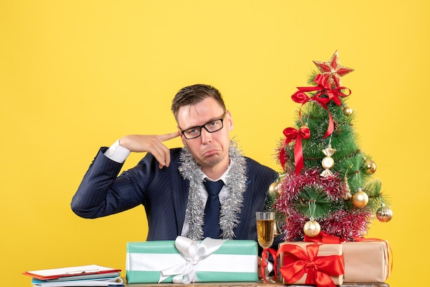 Front view of joyless business man sitting at the table near xmas tree and presents on yellow
