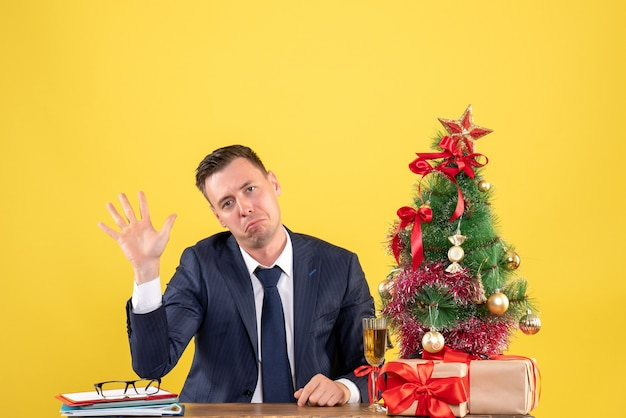 Front view of joyless man opening his hand sitting at the table near xmas tree and gifts on yellow