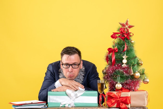 Front view of joyless man sitting at the table near xmas tree and presents on yellow