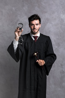 Front view judge in robe with handcuffs and gavel