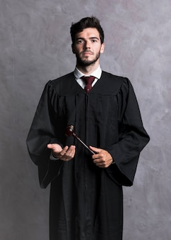 Front view judge in robe with wooden gavel