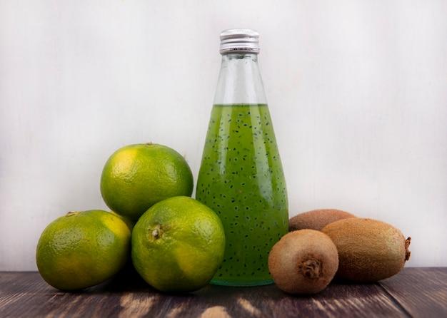 Bottiglia di succo di vista frontale con mandarini verdi e kiwi