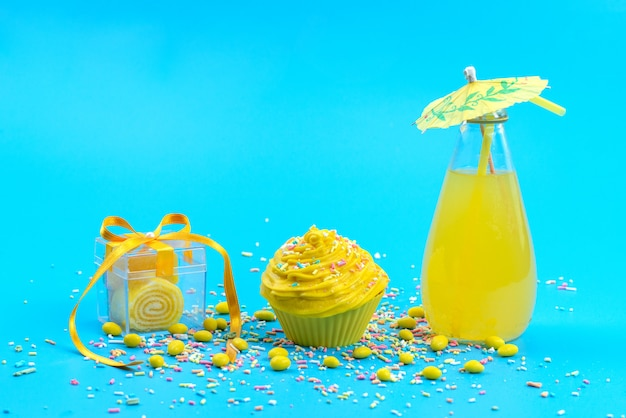 A front view juice and cake with candies on the blue desk cake biscuit color