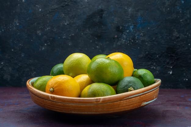 正面図ジューシーな柑橘類レモンとみかん、暗い床の柑橘類の熱帯のエキゾチックなオレンジ色の果実