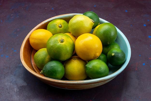 正面図ジューシーな新鮮な柑橘類レモンとみかんの暗い机の柑橘類の熱帯のエキゾチックなオレンジ色の果実