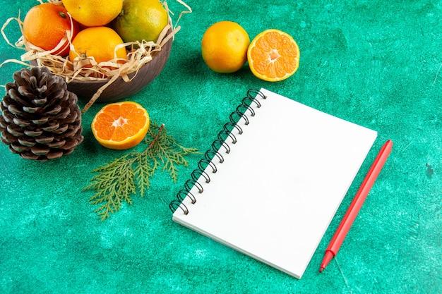 緑の背景色のエキゾチックな柑橘系の果物の写真のプレート内のジューシーな新鮮なみかんの正面図