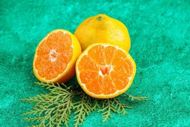 正面図緑の背景にジューシーな新鮮なみかんフルーツカラーエキゾチックな酸っぱい柑橘類の写真