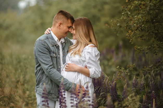 Front view of just married caucasian couple expecting baby, almost kissing in meadow with lupine flowers