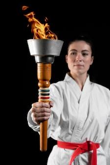 Vista frontale dell'atleta di karate che tiene la torcia