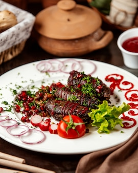 Front view khan kebab with tomato onion and pomegranate with herbs on a plate