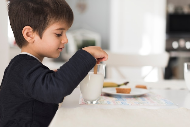 Front view kid dipping biscuit in milk
