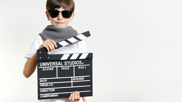 Front view kid holding clapperboard