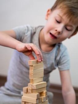 Вид спереди ребенок играет с деревянной башней игры