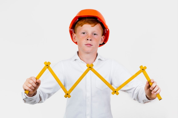 Front view kid posing as construction worker