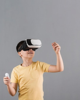 Front view of kid using virtual reality headset with copy space