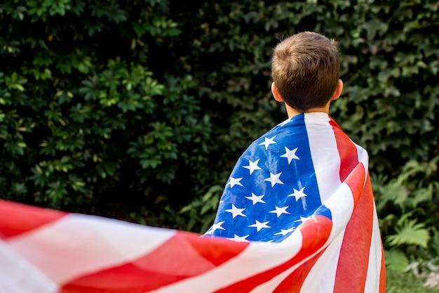 Вид спереди ребенок, носящий флаг сша