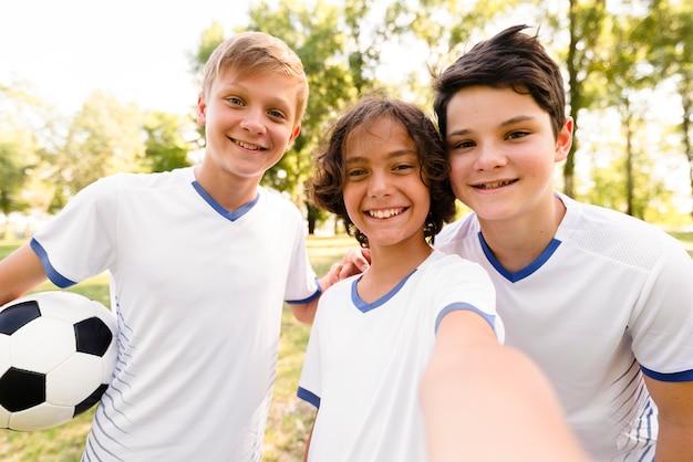 Bambini di vista frontale in abbigliamento sportivo di calcio che prendono un selfie