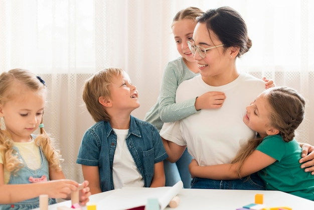 正面を向いた子供たちが先生を抱いて