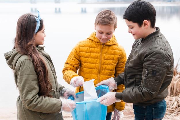 Vista frontale dei bambini con il sacchetto di plastica