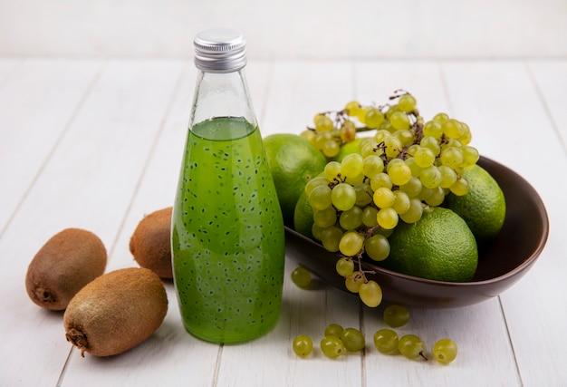 白い壁のボウルにリンゴとみかんのジュースのボトルとブドウの正面図キウイ