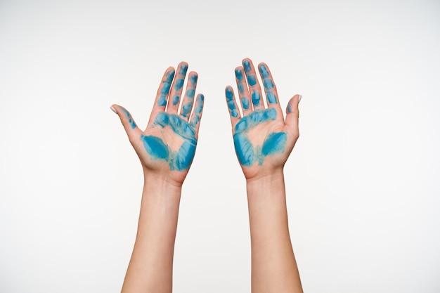 Vista frontale delle mani della signora dipinte con colore blu che viene sollevato durante la dimostrazione dei palmi, in posa su bianco. concetto di mani umane