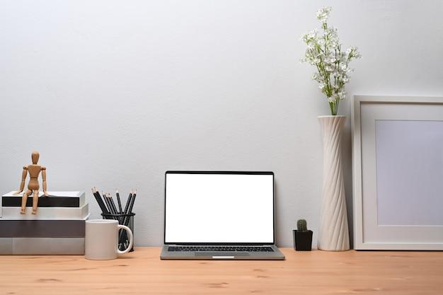 正面図のラップトップコンピューター、フォトフレーム、本、鉛筆ホルダー、木製の机の上のコーヒーカップ。