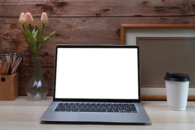 전면 보기 노트북 컴퓨터, 사진 프레임, 연필 홀더 및 흰색 테이블에 커피 컵.