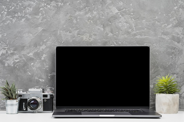 Front view laptop with plants and camera