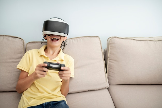 Front view laughing boy playing with vr glasses