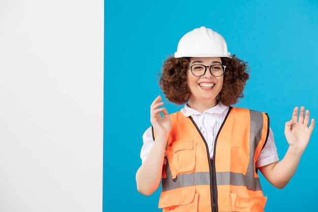 Front view laughing female builder in uniform on blue