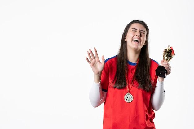 Вид спереди смеющаяся женщина-игрок с золотым кубком и медалью
