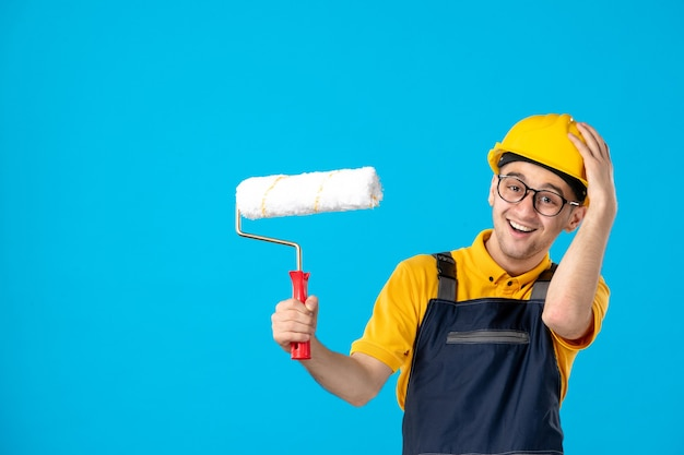 Costruttore maschio di risata di vista frontale in uniforme e casco sull'azzurro